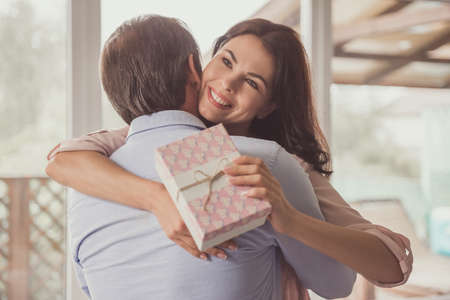 Couple at home. Handsome mature man is giving a present to his beautiful wife, she is hugging him and smiling