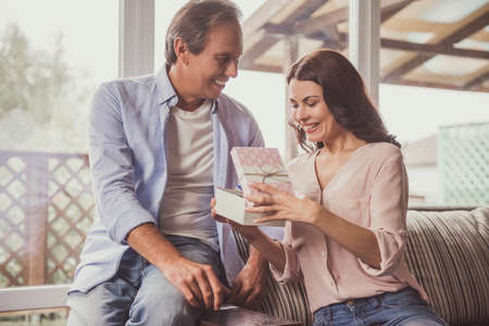 Couple at home. Handsome mature man is giving a present to his beautiful wife, both are smiling