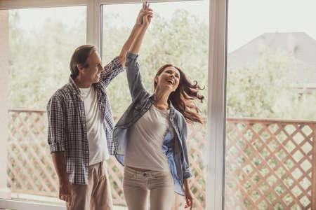 Het mooie gelukkige paar danst en glimlacht terwijl thuis het rusten
