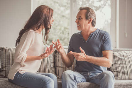 Couple of adults are quarreling while sitting on couch at home