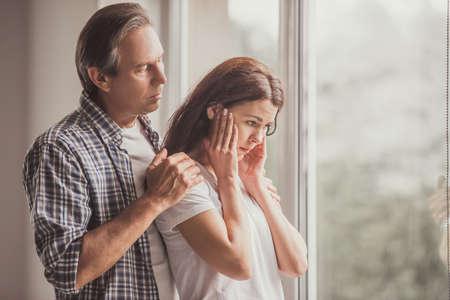 Stel thuis. De knappe rijpe mens kalmeert zijn verstoorde vrouw terwijl allebei zich dichtbij het venster bevinden