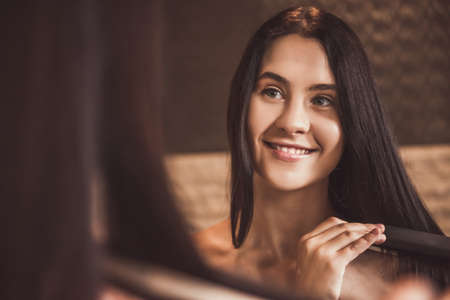 Attractive young woman in towel is using a hair straightener and smiling while looking into the mirror in bathroom Stock Photo