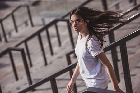bajando escaleras: Stylish dark-haired girl in casual clothes and glasses is looking at camera while going down the stairs outdoors