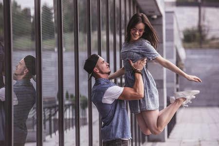 スタイリッシュな若いカップルが楽しんで、屋外を歩きながら笑みを浮かべて、男は、彼のガール フレンドを持ち上げて