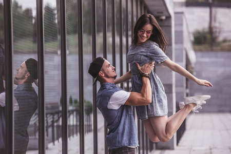 Stylish young couple is having fun and smiling while walking outdoors, guy is lifting his girlfriend