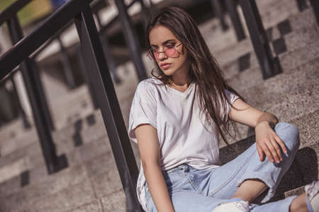 Stylish dark-haired girl in casual clothes and glasses is looking away while sitting on stairs outdoors Stock Photo