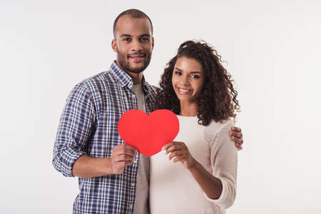 Beautiful Afro American couple holding a big red paper heart, looking at camera and smiling, isolated on white background