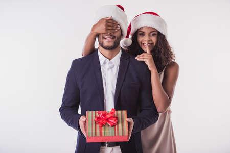 Pares afro-americanos elegantes em chapéus de Santa. Linda está cobrindo os olhos do namorado, mostrando sinal de silêncio, olhando para a câmera e sorrindo, isolado no branco