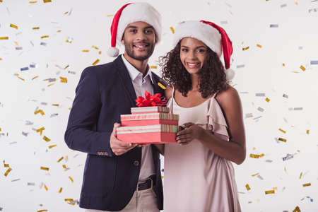 Beautiful Afro American couple in Santa hats and elegant clothes holding presents, looking at camera and smiling, on white background