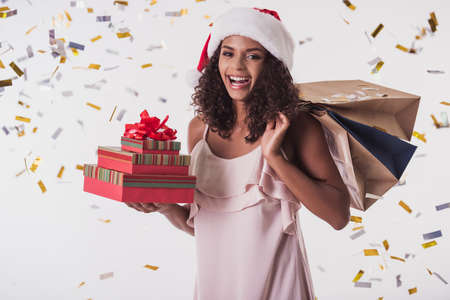 Beautiful Afro American girl in dress and Santa hat is holding presents, looking at camera and smiling, isolated on white Stockfoto