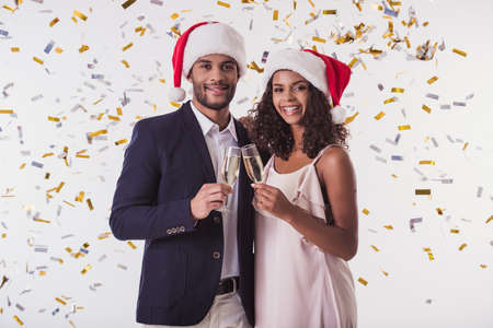 Elegant Afro Amerikaans paar in Kerstmanhoeden rammelende glazen champagne, bekijkend camera en glimlachend, op witte achtergrond