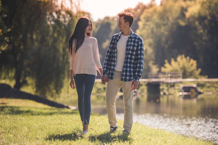 Beautiful young couple is holding hands and looking at each other while walking in the park