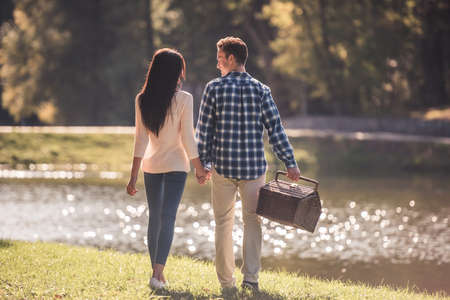 Back view of beautiful young couple holding hands while walking in the park, guy is carrying a picnic basket