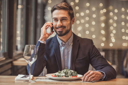 Handsome businessman in suit is talking on the mobile phone and smiling while sitting in restaurant Stock Photo
