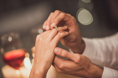 Cropped image of man putting on an engagement ring on his girlfriends finger while they sitting at the tablet in a restaurant