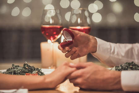Geerntetes Bild des Mannes einen Verlobungsring halten und zu seiner Freundin in einem Restaurant vorschlagen