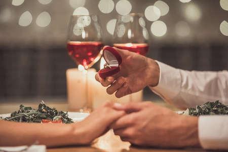 Imagen recortada de hombre sosteniendo un anillo de compromiso y proponer a su novia en un restaurante