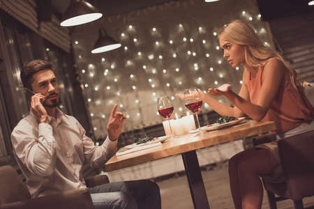 Beautiful young woman is annoyed while her boyfriend is talking on the mobile phone during their date in a restaurant Stock Photo