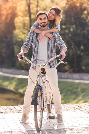 Beautiful young couple is having fun while riding a tandem bicycle in the park. Girl is hugging her boyfriend