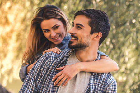 Beautiful young couple is hugging and smiling while resting in the park