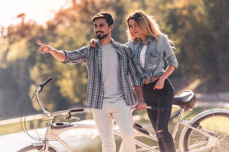 Beautiful young couple talking and smiling while standing near the tandem bicycle in the park