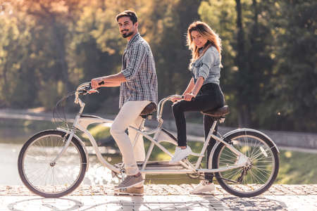 Beautiful young couple looking at camera and smiling while riding a tandem bicycle in the park