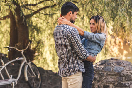 Beautiful young couple is hugging while resting in the park, a bicycle in the background Stock Photo