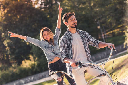 Beautiful young couple is having fun while riding a tandem bicycle in the park Stok Fotoğraf