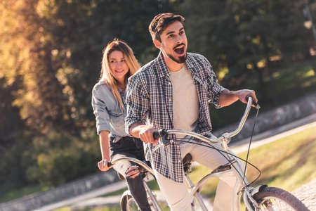 美しい若いカップルが公園でタンデム自転車に乗りながら楽しんでください。