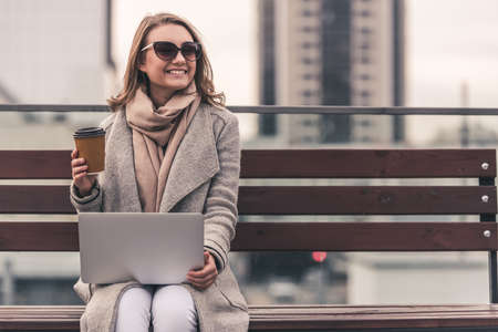 Beautiful girl in coat and sun glasses is drinking coffee, using a laptop and smiling while sitting on a bench outdoors Stockfoto