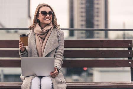 Schönes Mädchen im Mantel und in den Sonnenbrillen trinkt Kaffee, benutzt einen Laptop und lächelt beim auf einer Bank draußen sitzen