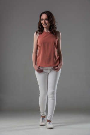 Full length portrait of attractive woman in smart casual clothes looking away and smiling, on gray background