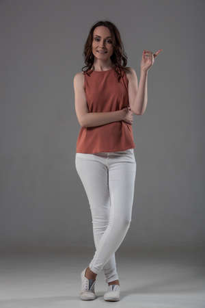 Full length portrait of attractive woman in smart casual clothes pointing, looking at camera and smiling, on gray background Stock Photo
