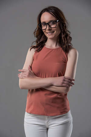 Attractive woman in smart casual clothes and eyeglasses is looking at camera and smiling while standing with crossed arms on gray background