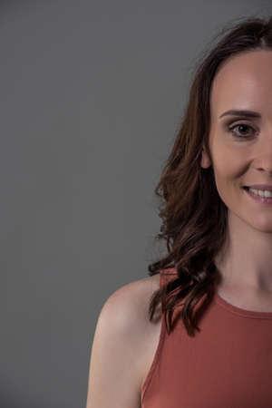 スマート カジュアルな服で魅力的な女性のトリミングされた画像をカメラを見て、笑みを浮かべて、灰色の背景に 写真素材
