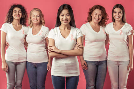 Women against breast cancer. Beautiful women of different ages and nationalities with pink ribbons on their chests are smiling, on red background