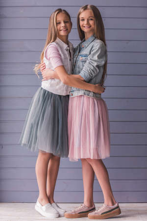 Full length portrait of two attractive teenage girls in dresses hugging, looking at camera and smiling, on gray wall background Archivio Fotografico