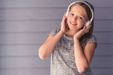Attractive teenage girls in headphones is listening to music, looking at camera and smiling, on gray wall background Archivio Fotografico