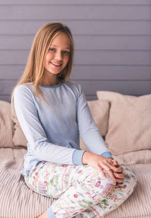 Attractive teenage girls in pajama is looking at camera and smiling while sitting on couch at home