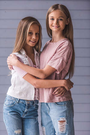 Two attractive teenage girls in casual clothes are hugging, looking at camera and smiling, on gray wall background