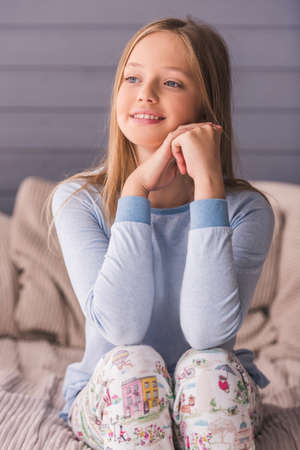 Attractive teenage girls in pajama is looking away and smiling while sitting on couch at home