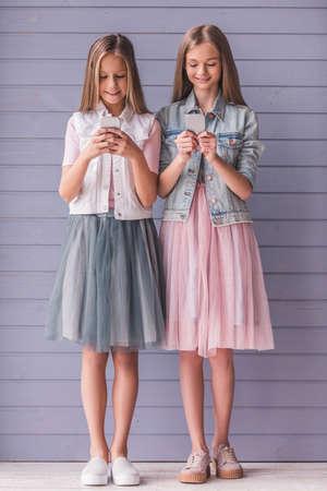 Retrato de cuerpo entero de dos adolescentes atractivas en vestidos con teléfonos inteligentes y sonriente, sobre fondo de pared gris