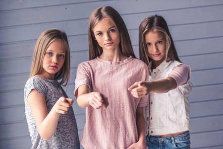 Trois adolescentes attrayantes dans des vêtements décontractés pointent vers la caméra avec des expressions de visage graves, sur fond de mur gris Banque d'images - 91795871