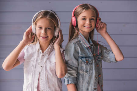 Two attractive teenage girls in headphones are listening to music, looking at camera and smiling, on gray wall background