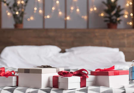 Happy holiday! Christmas presents on bed are waiting to be given. Gift boxes with ribbons