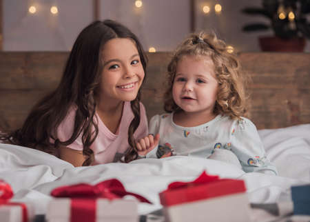 Cute little girls are looking at camera and smiling while sitting on bed at home on Christmas Stock Photo