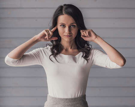Attractive young woman is covering her ears and looking at camera, on gray background Stockfoto