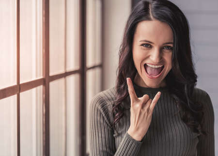 Attractive young woman is showing rock sign, looking at camera and smiling while standing in the room