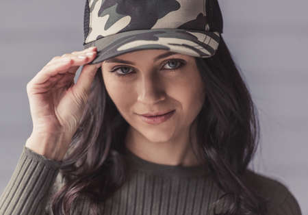 Attractive young woman in camouflage cap is looking at camera and smiling, on gray background