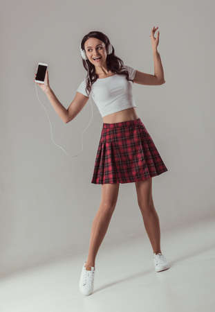 Full length portrait of attractive young woman in top and skirt listening to music using a smartphone and smiling, on gray background
